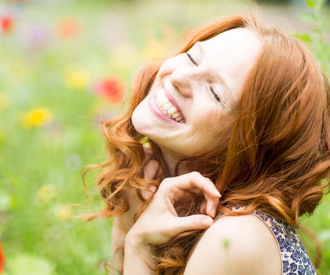 schöne lachende Frau in der Blumenwiese